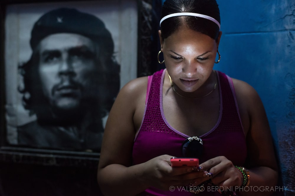 A woman checks her smartphone in front of a picture of Che Guevara in Havana, Cuba on the late afternoon of 29 December 2015. Starting in 2015 the government owned telecomunication company, ETECSA, began installing wi-fi spots in central parks of Cuban cities. For the first time Cubans have access to the outside world through their devices. This woman was aware of the photographer. This photo was not staged.